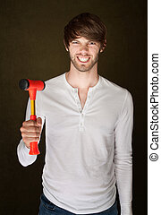 Man Holds Mallet - Smiling young Caucasian male with red...