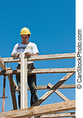 Construction worker on scaffold busy on formwork preparation