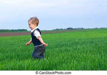 A beautiful little boy runing in the grass