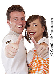 Happy Bavarian man and woman with dirndl hold thumbs up