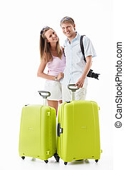 Smiling couple - An attractive couple with their suitcases...