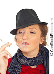 Nonchalant woman with hat smoking