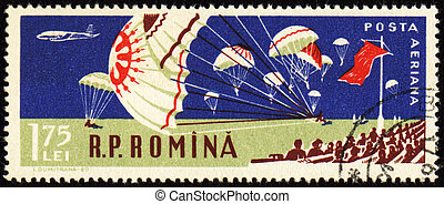 Parachutists landing in stadium on post stamp - ROMANIA -...