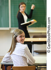 School child with a teacher in the classroom. The student...