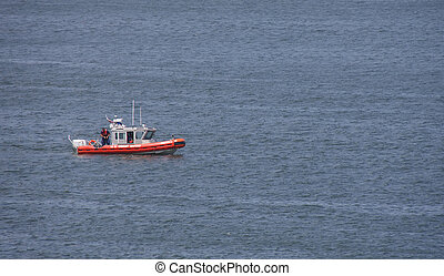 Coast Guard Checking Weapon - A Coast Guard boat in a harbor...