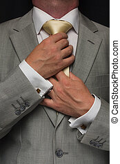 Man adjusting tie