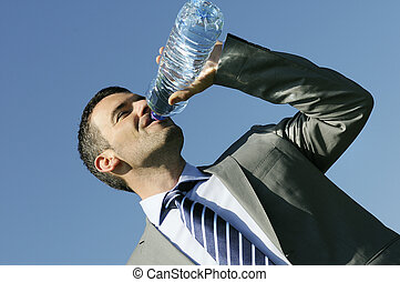 businessman in suit is drinking fresh water in a bottle