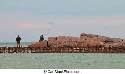 Two fishermen on rusty pier