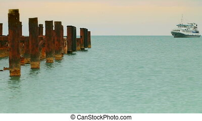 rusty destroyed pier on the background a ship