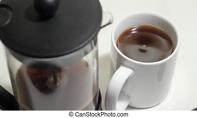 Coffee. - Cup  of hot coffee and French press.