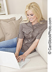 Young Blond Woman Using Laptop Computer At Home on Sofa