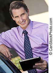 Successful Businessman Using Tablet Computer or iPad - A...