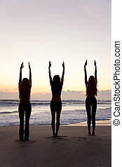 Three Women Practicing Yoga on Beach At Sunrise or Sunset -...