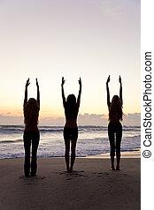 Practicar, tres, ocaso,  yoga, playa, o, salida del sol, mujeres