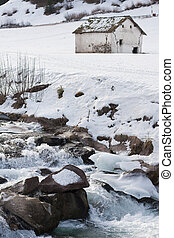 frozen river flowing with farmhouse