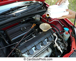 Adding Motor Oil to Car 2 - Male adding oil with a funnel...