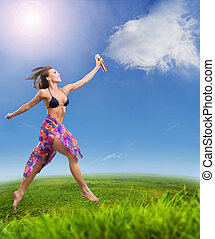 Young beautiful woman jumping on a summer meadow