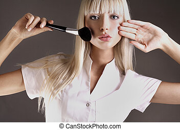 Attractive blonde with face powder brush