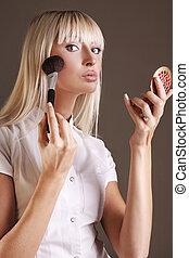 Young female beauty applying face powder