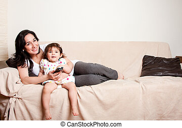 Mother and daughter watching TV - Beautiful happy family...