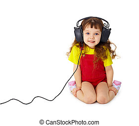 Child listens attentively to music on white - The child sits...