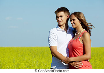 Dates - Image of happy couple in yellow meadow embracing