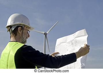 engineer - technician reading a plan on a  wind turbine site