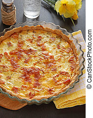 French pie Quiche Lorraine On the table with flower and...