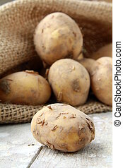 Bag of organic potatoes on a wooden background