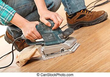 sander at work - detail of carpenter at work with sander on...
