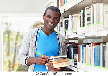 young african man smiling in library - african american male...