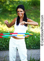 hula hoop - woman rotates hula hoop on nature background