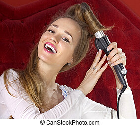 young girl curling her hair - happy beautiful young girl...