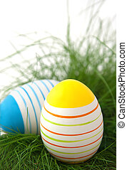 Striped easter eggs in green grass on white background