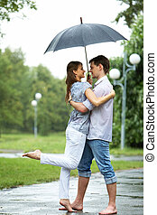 Romance - Portrait of woman and man embracing under umbrella...