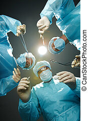 Saving a patient - Three surgeons bending over a patient...