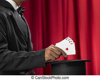 Magician make performance with card deck and top-hat