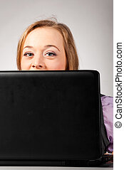 woman with laptop - woman is looking out of laptop at office