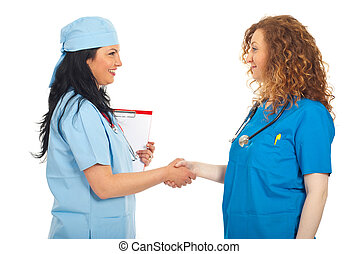 Doctors women hand shake - Two cheerful doctors women giving...