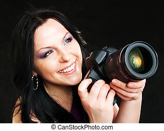 photographer woman holding camera over dark background -...