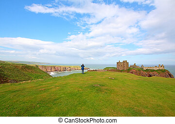 A tourist at Dunnottar Castle, Stonehaven, Scotland -...