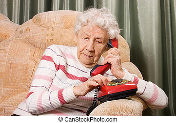 The elderly woman speaks on phone - The elderly woman speaks...