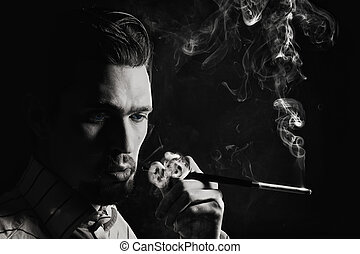Studio portrait of a young man smoking a cigarette on a...