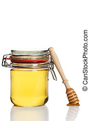 honey covered honey dipper leaning at a honey jar on white...