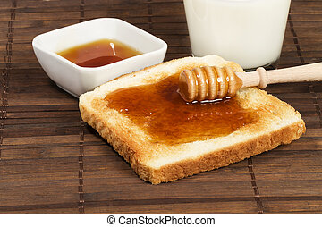 honey with honey dipper on a toast with a glass of milk and...