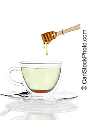 honey drops from a honey dipper in glass cup with green tea...