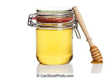 honey covered honey dipper leaning at a honey jar on white...