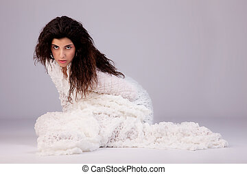 beautiful young woman sitting on the floor, wrapped in a white blanket, studio shot