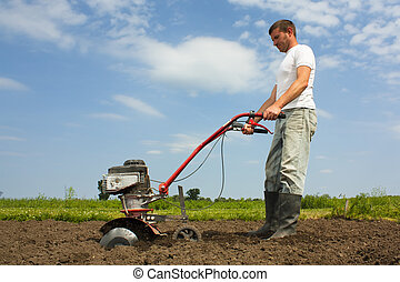 Working farmer - Man using cultivator or rotovator to till...