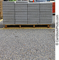 A pallet full of gray landscape bricks for patios and...